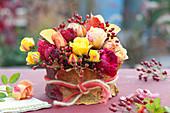 Kleines Gesteck aus Rosen und Hagebutten