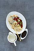 Gesunde Frühstückszutaten - Milch, Quinoaflocken, Kokosflocken, Trockenfrüchte, Samen und Nüsse