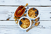 Top view of delicious granola and healthy breakfast ingredients - honey, fresh blueberries and nuts on white grunge background