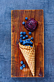 Fresh blueberries in waffle cones and homemade sorbet on vintage wooden board over dark stone background