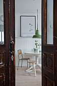Blick durch alte Kassettentür auf Esstisch vor verkleideter Wand