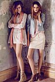 Zwei brünette Frauen in pastellfarbenen Outfits in Zimmerecke mit abgeblätterter Farbe