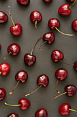 Cherries on a black surface (seen from above)
