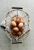 Fresh brown hen's eggs in a wire basket (seen from above)