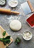 Stillleben mit Teigling und Pizzazutaten (Aufsicht)