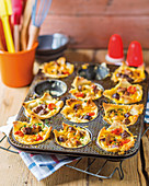 Mini bread quiches with tomatoes, grilled meat and cheese