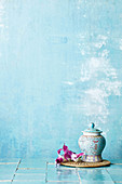 A decorated Asian porcelain vase and orchid blossoms against a blue background