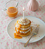 A birthday pancake-cake with caramel sauce and colourful sugar pearls
