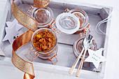 Eingemachte Tomaten in weihnachtlich dekorierten Bügelgläsern