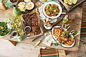 Gedeckter Tisch mit gegrilltem Fleisch, Garnelen, Süsskartoffeln und Salat (Italien)