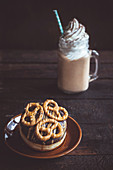 Sweet donuts with pretzels on top and coffee, selective focus