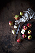 Apples on a plate against a dark wooden background (top view)