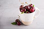 Fresh sweet cherries in a ceramic mug