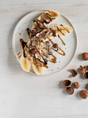 Halved bananas with hazelnuts, hazelnut butter and chocolate sauce