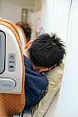 Passenger sleeping in economy class airline cabin