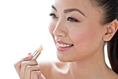 Woman applying lipstick portrait