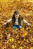 Girl sitting in a pile of Autumn leaves