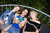 Three young women lying on trampoline