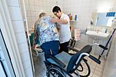 Nurse aiding an elderly woman to the toilet
