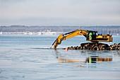 Bulldozer excavating coast