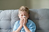 Young boy blowing his nose on a tissue