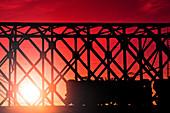 Train crossing bridge at sunset