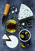 Healthy food background with cheese variety, olive oil, olives and fresh herbs over dark vintage texture