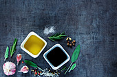 Top view of Olive oil and vinegar with peppercorns, sea salt, garlic and rosemary on dark vintage background