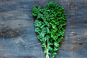Raw green curly kale on rustic wooden background