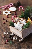 Lebkuchenplätzchen und Zuckerstangen in dekorativem Holzschlitten