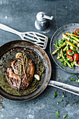 Rib-eye steak with a green asparagus and herb salad