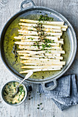 White, oven-baked asparagus with a potato and chive salsa