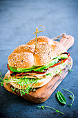 A turkey sandwich with cress, avocado and grilled peppers