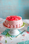 Rhubatb cake with swiss buttercream and pink meringues on a cake stand