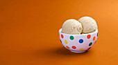 Two scoops of caramel ice cream in a spotted bowl