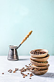Variety of different coffee beans and spices in wooden bowls in stack over grey table