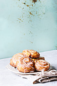 Plate of homemade glazed puff pastry cinnamon rolls on cloth over grey table