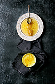 Honeycombs in liquid honey on white vintage plate and cup of turmeric latte on cloth over black texture background
