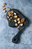 Salted caramel fudge candy served on black wooden board with fleur de sel, caramel sauce and caramelized walnuts