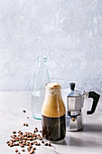 Bottle of fizzy iced Coffee espresso with bottle of sparkling water, coffee maker and roasted beans over grey table