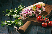 Beef and vegetables sandwich with sliced meat, pickled cucumber, green salad on wooden cutting board over dark kitchen table