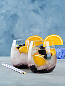 Sparkling cocktail with blackberries and oranges over blue background