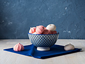 Pink and white meringues in a blue bowl