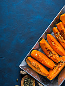 Raw sliced pumpkin ready to be cooked on a tray over blue background
