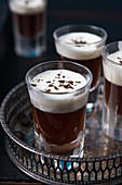 Glasses of coffee schnapps with cream on a tray