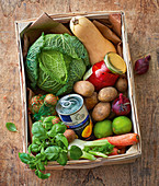 A vegetable box with canned fruit and preserved peppers