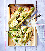 Baked fennel with cheese and nuts on a baking tray