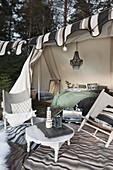 Campingstühle und runder Tisch auf Teppich vor eingerichtetem Zelt mit Lichterkette