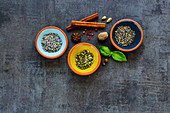 Dry tasty herbs and spices in pinch bowls on dark concrete background