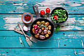 Fried baby potatoes in old cast iron pan and salad with tomato and arugula in bowl on turquoise wooden background